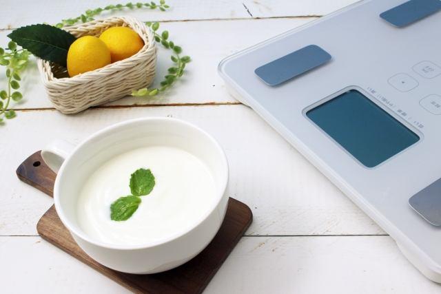 白い木のテーブルにあるレモンとヨーグルトと体重計