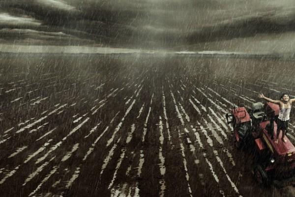 boy on top of a tractor enjoying rain