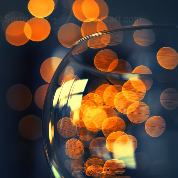 Orange bokeh behind wine glass