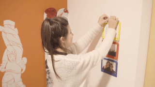 Girl hanging photos on a fridge