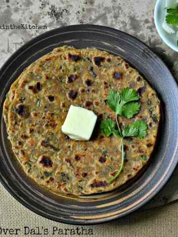 Dal's paratha served on a black plate with butter and fresh herbs.