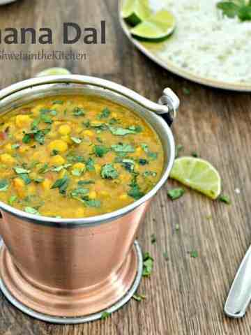 Chanal dal served in a brass pot and garnished with fresh herbs