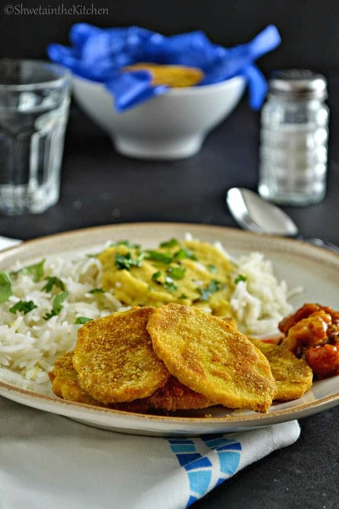 The Indian potato slices served with dal and pickle on a white plate