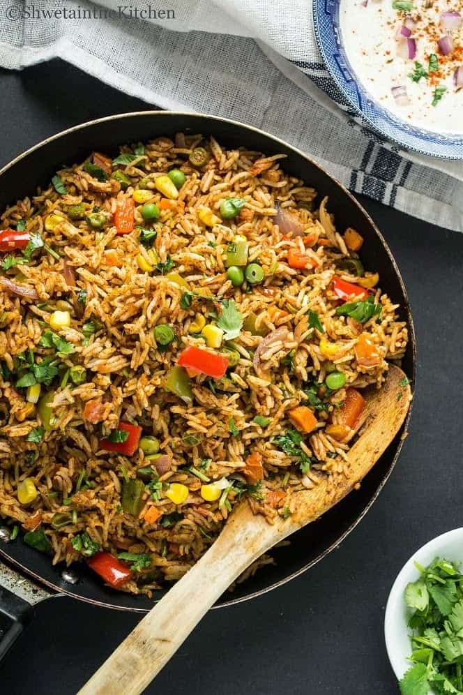 Tawa pulao in a skillet with a wooden spatula