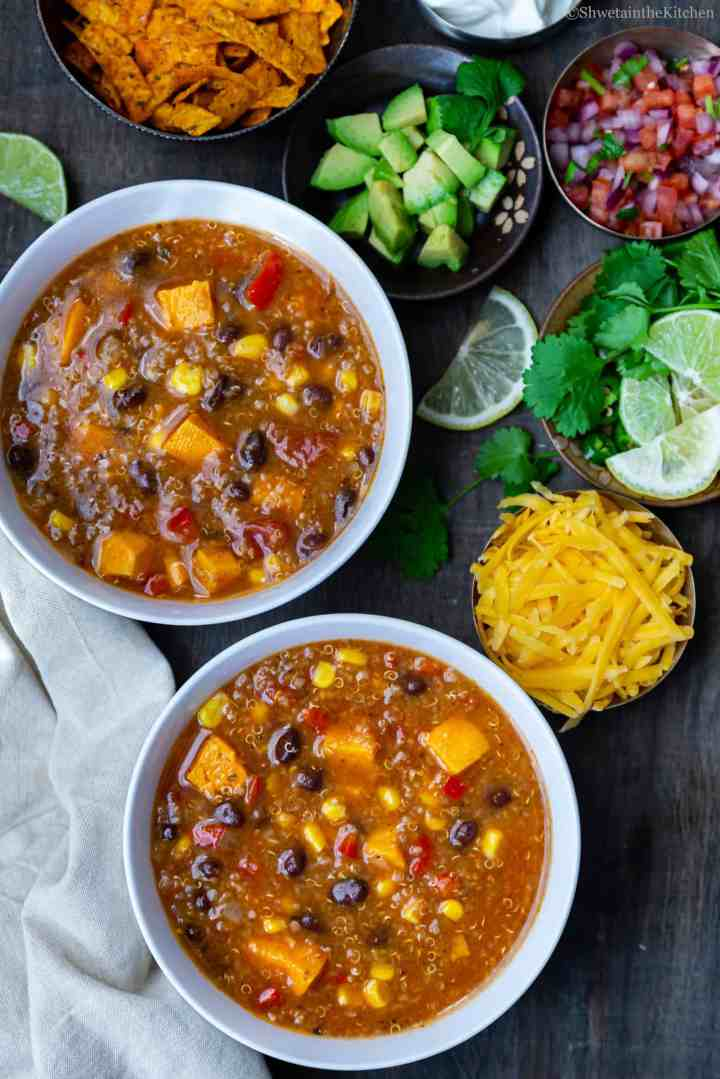Quinoa Enchiladas Soup served in two bowls with toppings on the side.