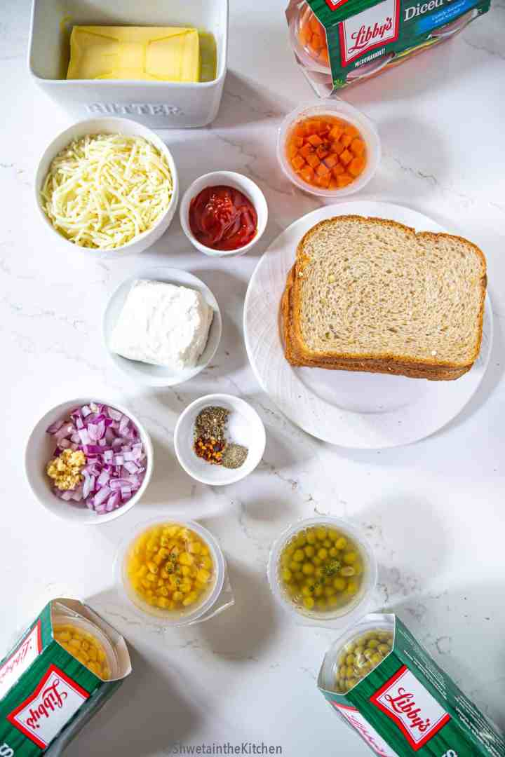 All the ingredients for vegetable sandwich laid on a white surface