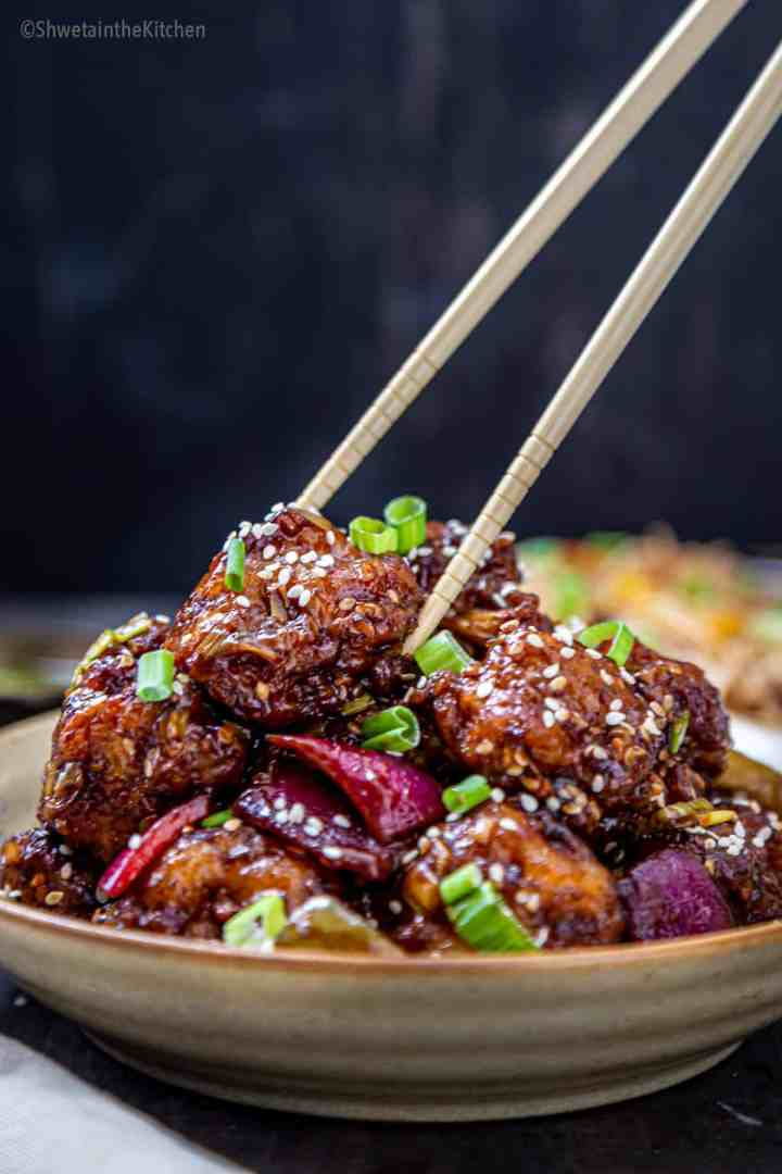 Gobi Manchurian dry stacked on plate and picked by chopsticks