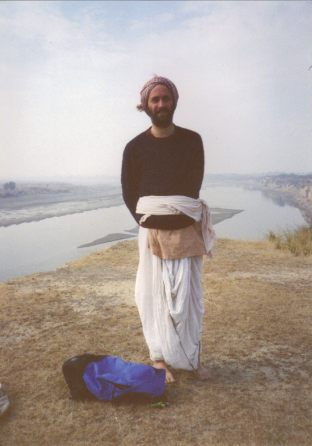 A young dhoti and sweater clad Shyamdas by a body of water, likely Yamunaji