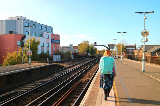 Kariss on a train station with her Cabin Zero backpack