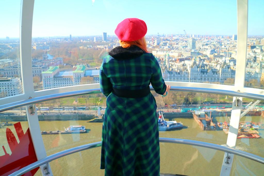 women in green dress looking out from a London Eye casual one of London Observation Points