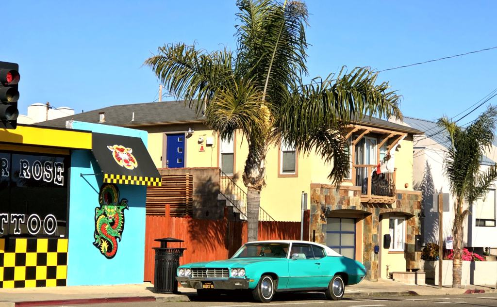 green american car in front of a tattoo shop in California to represent a dream US Road Trip