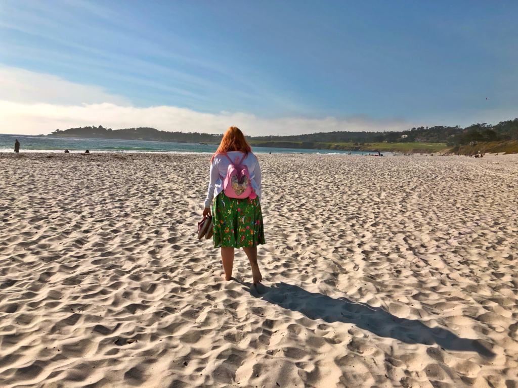 woman in cardigan and green dress walking on the beach in Carmel by the Sea