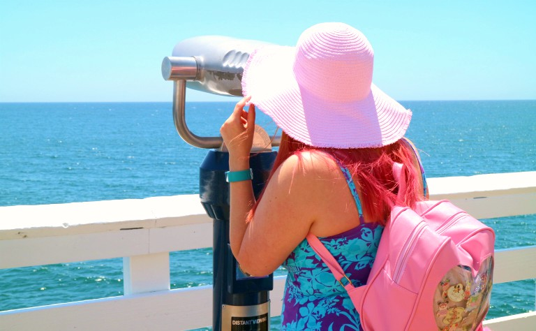 woman in a pink hat looking into a view finder into the sea at Malibu pier
