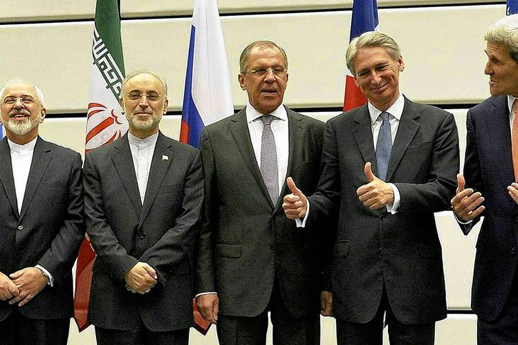 U.S. Secretary of State John Kerry, far right, and U.K. Foreign Secretary Philip Hammond, second from right, gesture toward Iran Foreign Minister Javad Zarif, far left. Iran's Ali Akbar Salehi is second from left. Russia Foreign Minister Sergei Lavrov stands center.