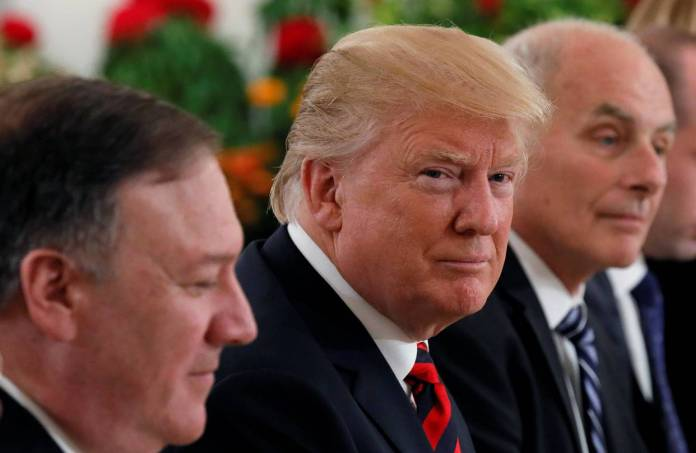 President Donald Trump is flanked by Secretary of State Mike Pompeo, left, and White House chief of staff John Kelly at a lunch in Singapore on Monday.