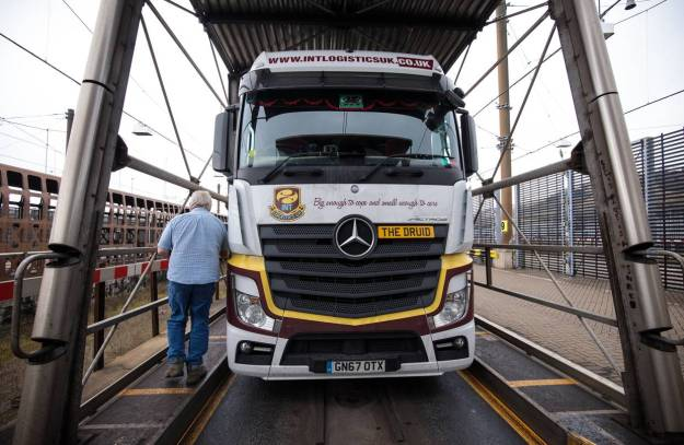 A truck driver returns to his vehicle as the Eurotunnel Freight train carrying it and others arrives in Folkestone, England, in March. Trucks exiting the tunnel don't have to stop as they head to their British destinations.