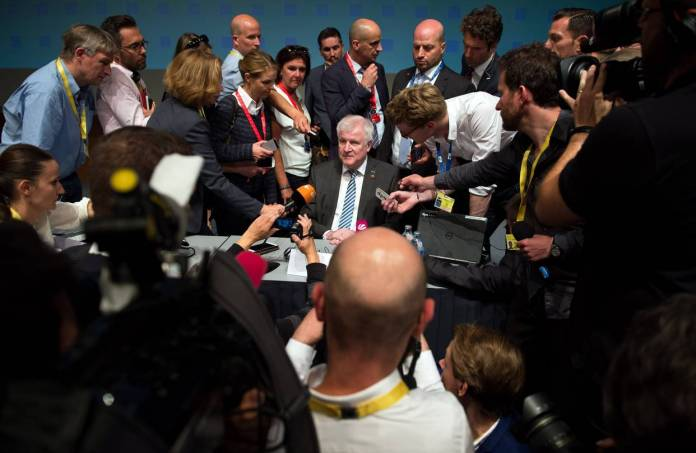 German Interior Minister Horst Seehofer answers reporters' questions at a meeting of justice and home affairs ministers in Innsbruck, Austria. The ministers failed to agree to redistribute migrants across the EU.