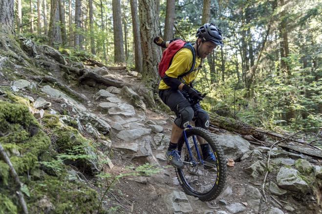 To navigate rocky terrain on one wheel, Ryan Kremsater holds a handle beneath his seat with one hand and uses the other to help stay balanced.
