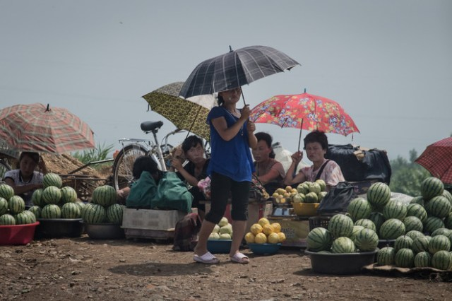 Women sell fruit beside a road on the outskirts of Sinchon, North Korea, south of Pyongyang, as markets sprout in the nominally socialist country.