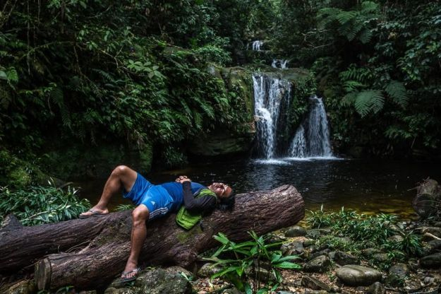 Ernesto Jicca, a local guide, and motorboat driver, rest by a waterfall.