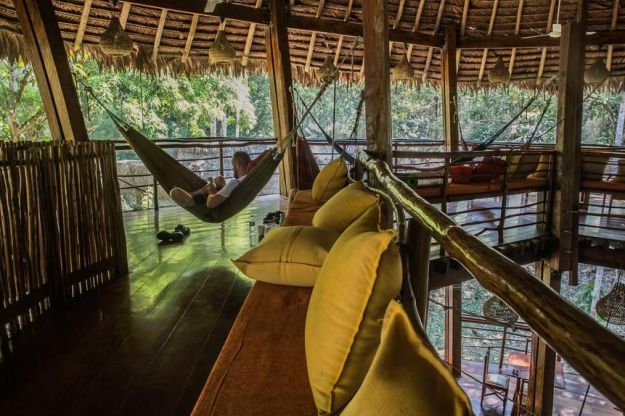 A young man rests in a hammock at the Treehouse Lodge's Relaxation Area.