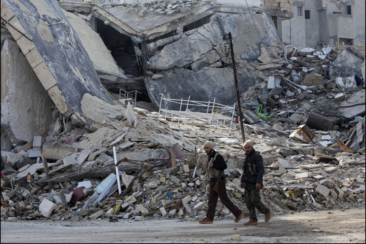 Militiamen walk through the destroyed city center.
