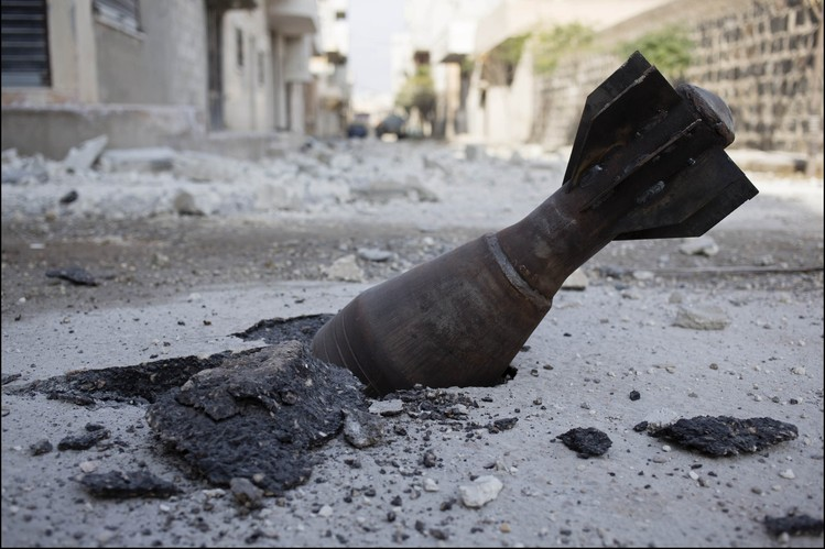 A crater is formed by an unexploded munition in the besieged city of Kobani.