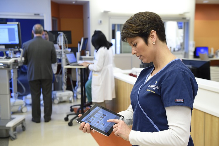 Nurse Rhonda Wyskiel carries a tablet computer during rounds in the surgical intensive care unit at The Johns Hopkins Hospital to quickly gauge whether her patients are at risk of any harms.