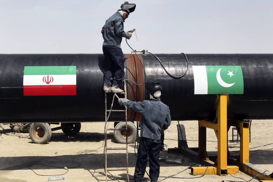 Iranian workers weld two pipes together in 2013, at the start of construction on a pipeline to transfer natural gas from Iran to Pakistan in Chabahar, Iran.