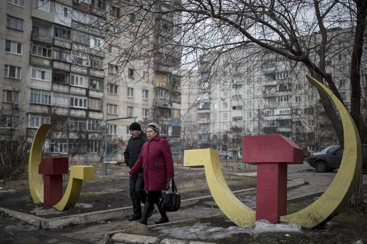 Residents walk past Soviet-era hammer and sickle sculptures outside an apartment building damaged by shelling in January in Mariupol.