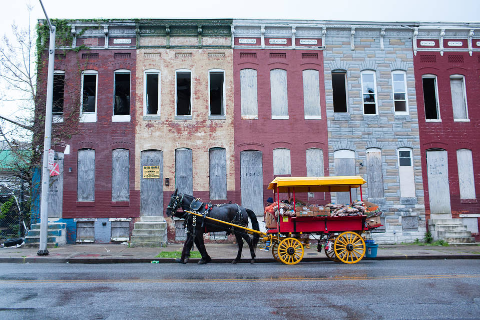 A man leads a horse-drawn cart, from which he sells produce, along Mosher Street in the Sandtown-Winchester neighborhood of Baltimore, Md., in April.