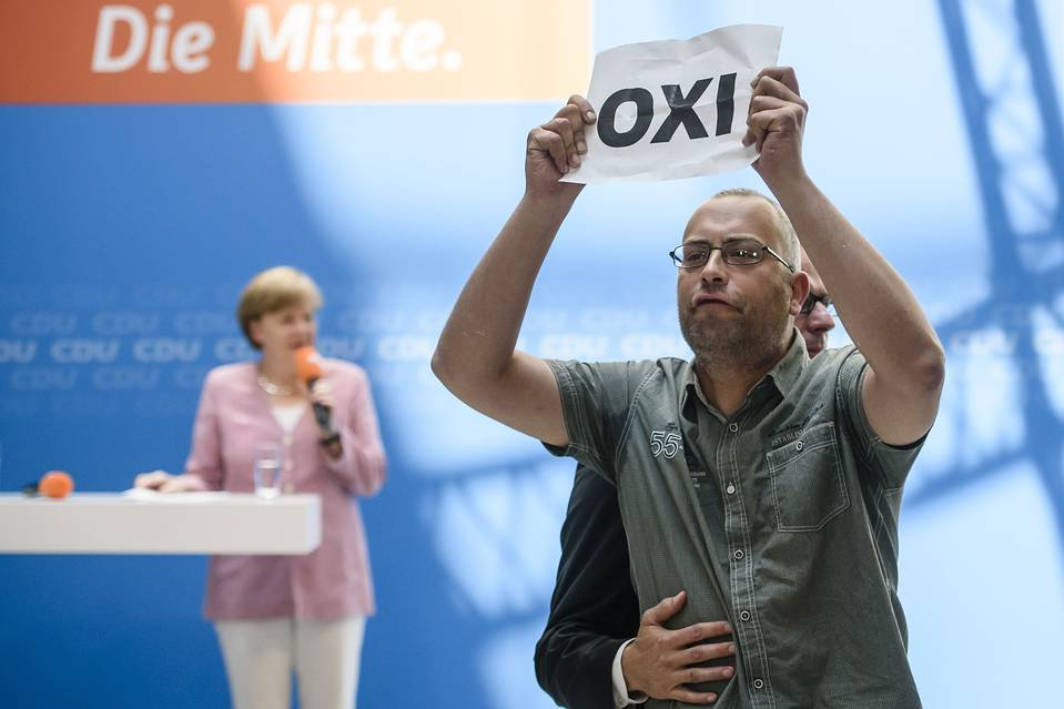 A protester holds a sheet with the Greek word for 'No' during an open house presentation of Germany's conservative Christian Democratic Union on Saturday in Berlin, while Chancellor Angela Merkel speaks in the background.