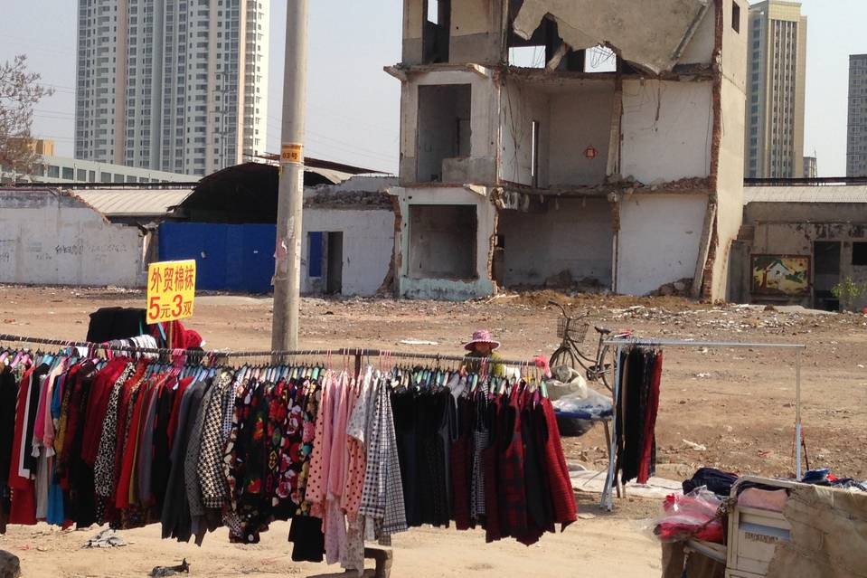 Vendors sell clothing at a makeshift market in downtown Tengzhou, a city of 1.5 million that has been hit hard by layoffs and factory closures.