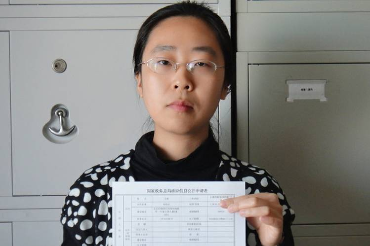 "One of China's ""Feminist Five,"" Wang Man, shown here in 2012 with a paper demanding financial disclosure from the Chinese state administration of taxation, was recently released from custody. The five activists complained to the U.N. that it is now impossible for women's groups to work with the Chinese government"