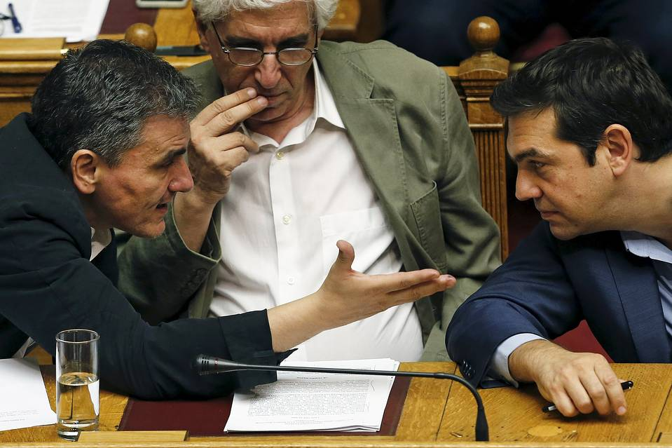 """Greek Prime Minister Alexis Tsipras, right, listens to Finance Minister Euclid Tsakalotos as Justice Minister Nikos Paraskevopoulos, center, looks on during a parliamentary session in Athens on July 23. """"Syriza's problems are not going to become the country's problems,"""" Mr. Tsipras said in a radio interview Wednesday, referring differences within the party."""