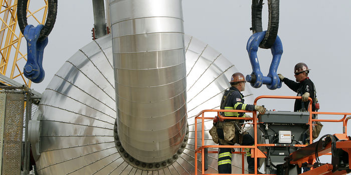 A fractionator tower is lifted in place at a natural gas processing complex in Mont Belvieu, Texas, on March 8, 2013.
