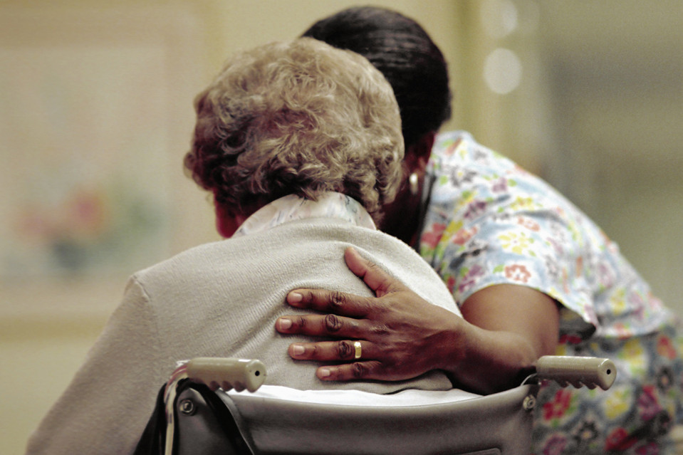 A nurse cares for an elderly woman in a nursing home.