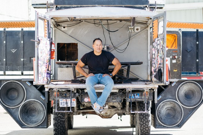 Mr. Hwang in the back of the Mog, surrounded by four fold-out subwoofers.