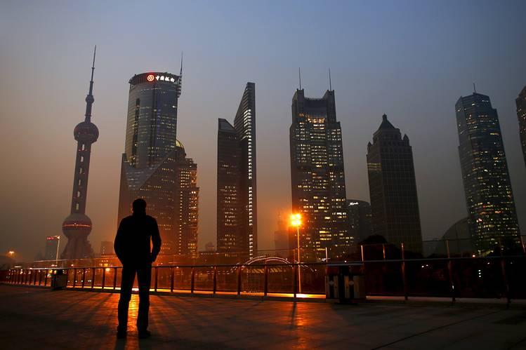 Homem observa o distrito financeiro de Pudong, em Xangai. Pela primeira vez em anos, as empresas de mercados emergentes estão deixando de pagar suas obrigações com mais frequência que seus pares nos Estados Unidos.