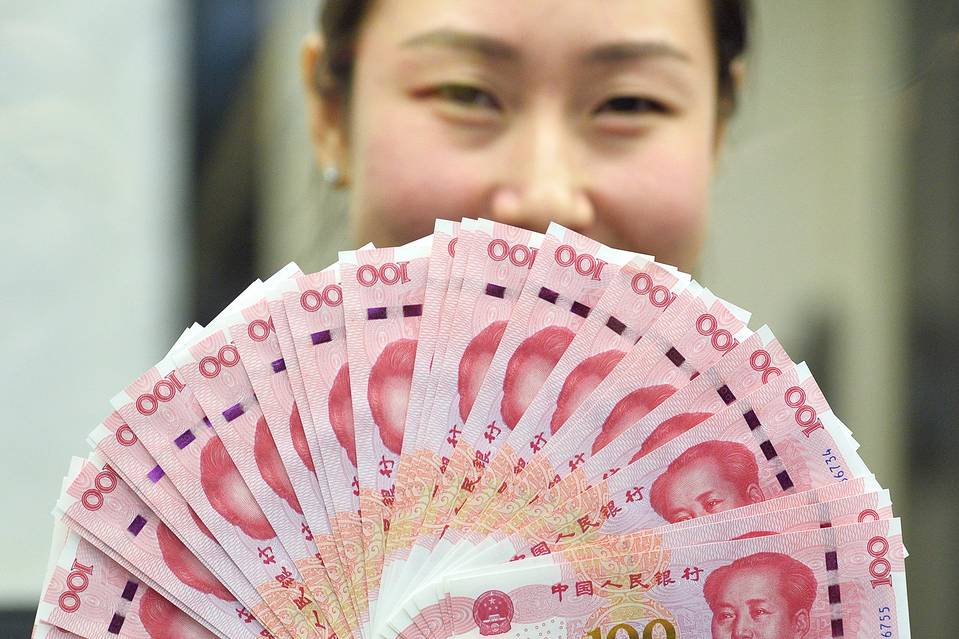 A Bank of Communications bank staff member displayed new 100-yuan banknotes in Beijing on Nov. 12.