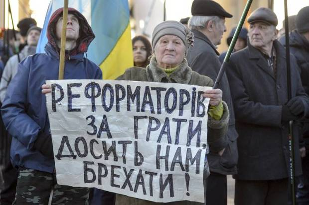 An antigovernment rally in Kiev on Tuesday. The sign says, 'Put the reformers behind bars. Enough lying to us.'