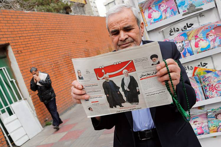 "An Iranian man holds a copy of the daily Shargh newspaper with a headline reading ""Decisive victory for the reformist"" in Tehran, 28 Feb."