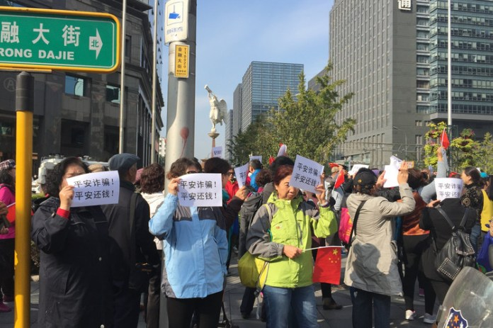 Protesters outside Ping An Insurance's Beijing headquarters in October held signs saying: 'Ping An cheats! Ping An, return the money!'