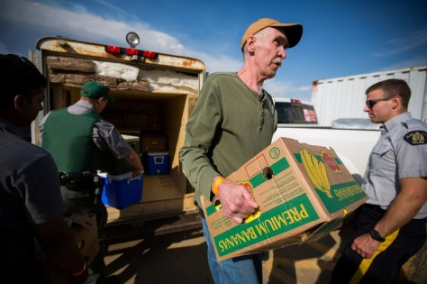 Volunteers help carry food into a community center in Anzac.