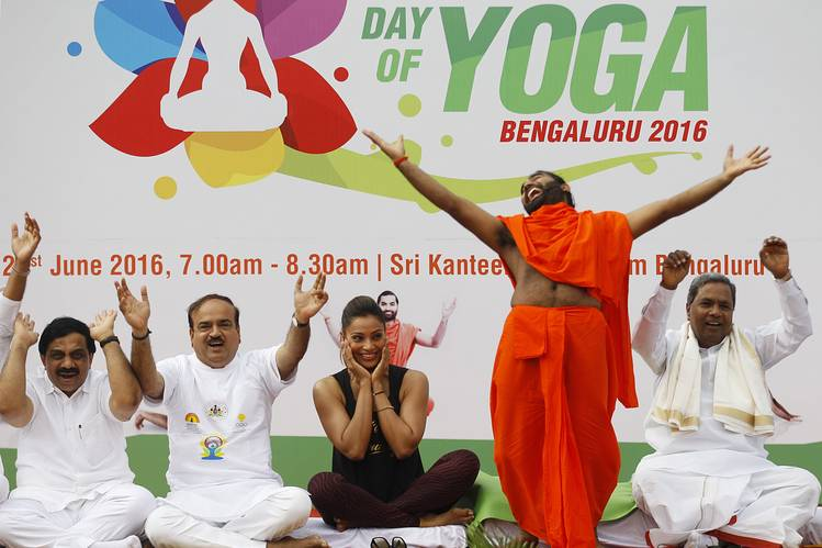 Bollywood actress Bipasha Basu, third left, laughed as yoga guru Sri Vachananand Swamiji, second right, performed yoga at an event in the southern Indian city of Bangalore Tuesday.