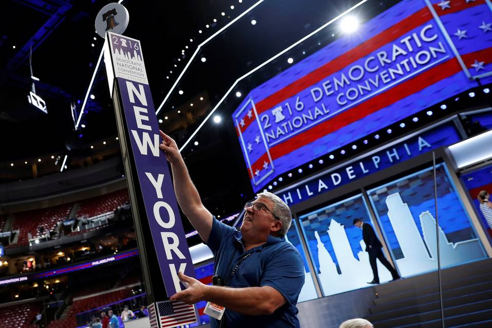 A worker adjusts the sign for the New York delegation on the floor amid preparations for the 2016 Democratic National Convention in Philadelphia.