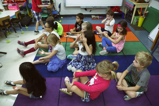 Children in a kindergarten class at Howard Early Childhood Center in San Antonio listen and apply sunscreen as their teacher Marianne DiSabato reads a story about the weather.