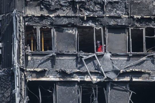 A firefighter peers out from Grenfell Tower in London following the June fire that killed at least 80 people.