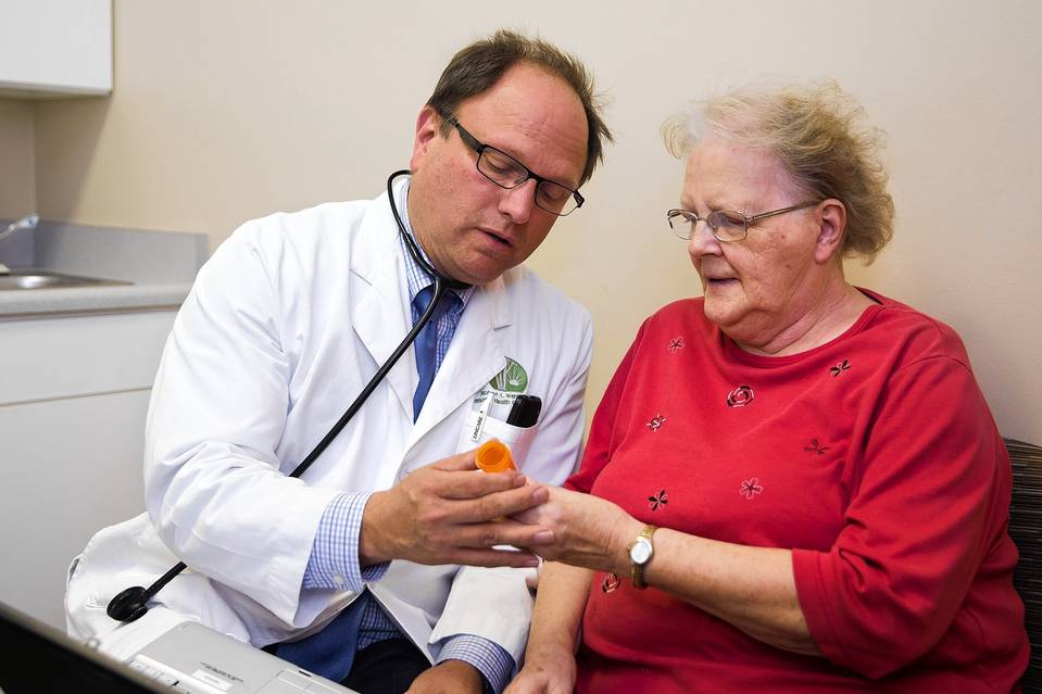 'We're hoping [the switch to the new codes] will be like Y2K,' when computer systems managed the date switch to 2000, says Dr. Robert Wergin, president of the American Academy of Family Physicians, shown with a patient in 2014.