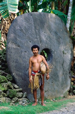 伝統的な衣装をまとい、ヤップ島で今も使われる石貨の前に立つ男性